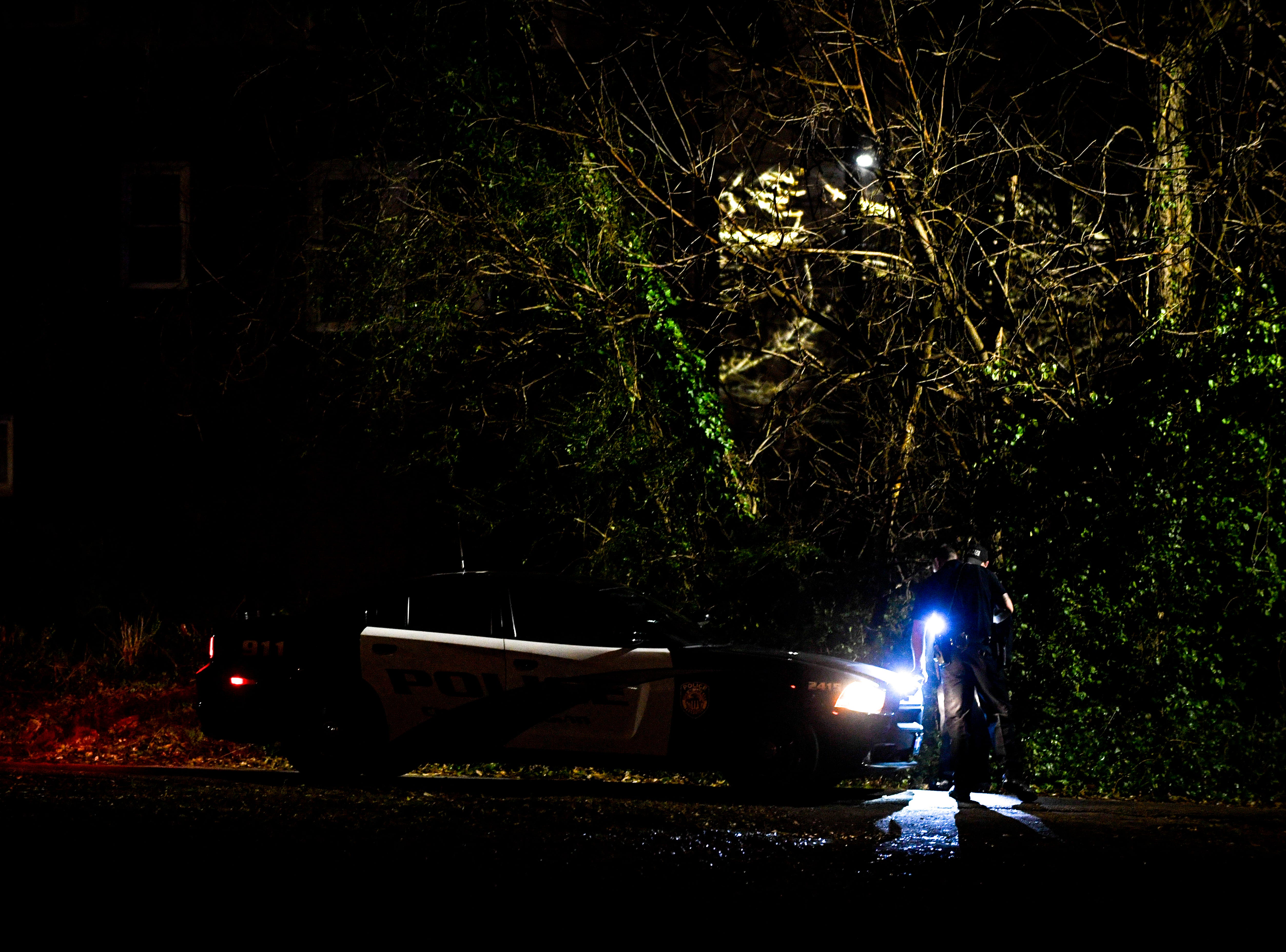Jackson Police Officers search between homes after a short pursuit while trying to serve a warrant at N Highland and Arlington, in Jackson, Tenn., on Friday, March 1, 2019.