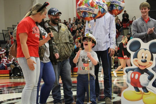 Lucas Jaeger, 6, reacts after being told he's going on a Disney cruise during halftime of Union University's women's basketball game on Thursday.