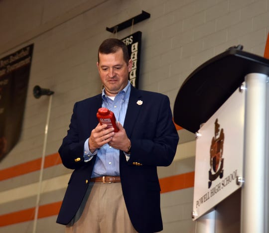"""Dr. Chad Smith admires his award, a bottle of Old Spice body wash, during """"The Emorys"""", a ceremony recognizing the top 10 students at Powell High."""