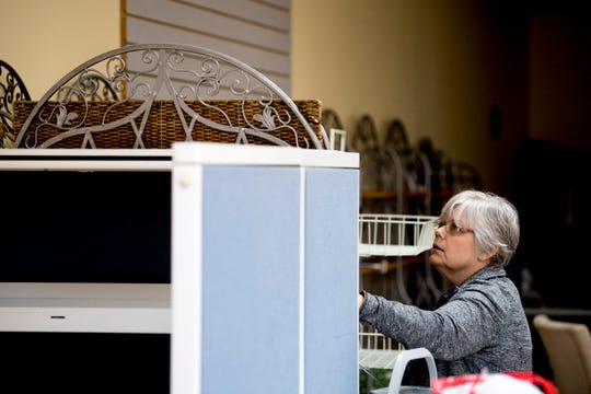 Debi Hammond, salesperson at The Yarn Haven, helps move shelving at the store on Friday. Nearly a quarter of the store's inventory, including furniture and paperwork, was lost in the recent flooding.