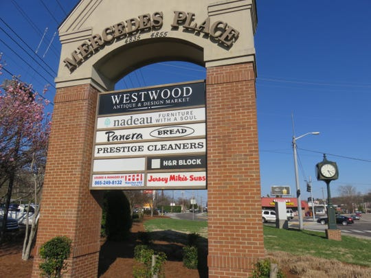 Bearden clock sits alongside Kingston Pike, a few feet from Mercedes Place shopping center sign.