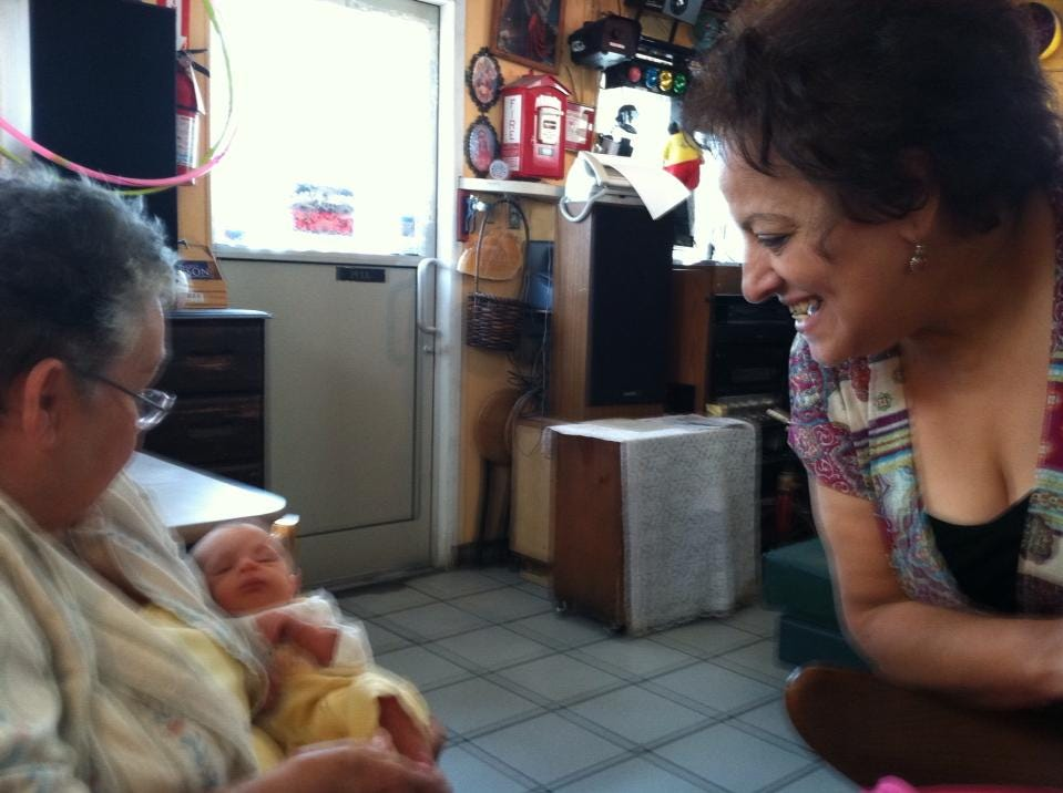 South Knoxville resident and King Tut Grill regular Sara Baskin, left, holds a friend's newborn son as restaurant owner Seham Girgis looks on.