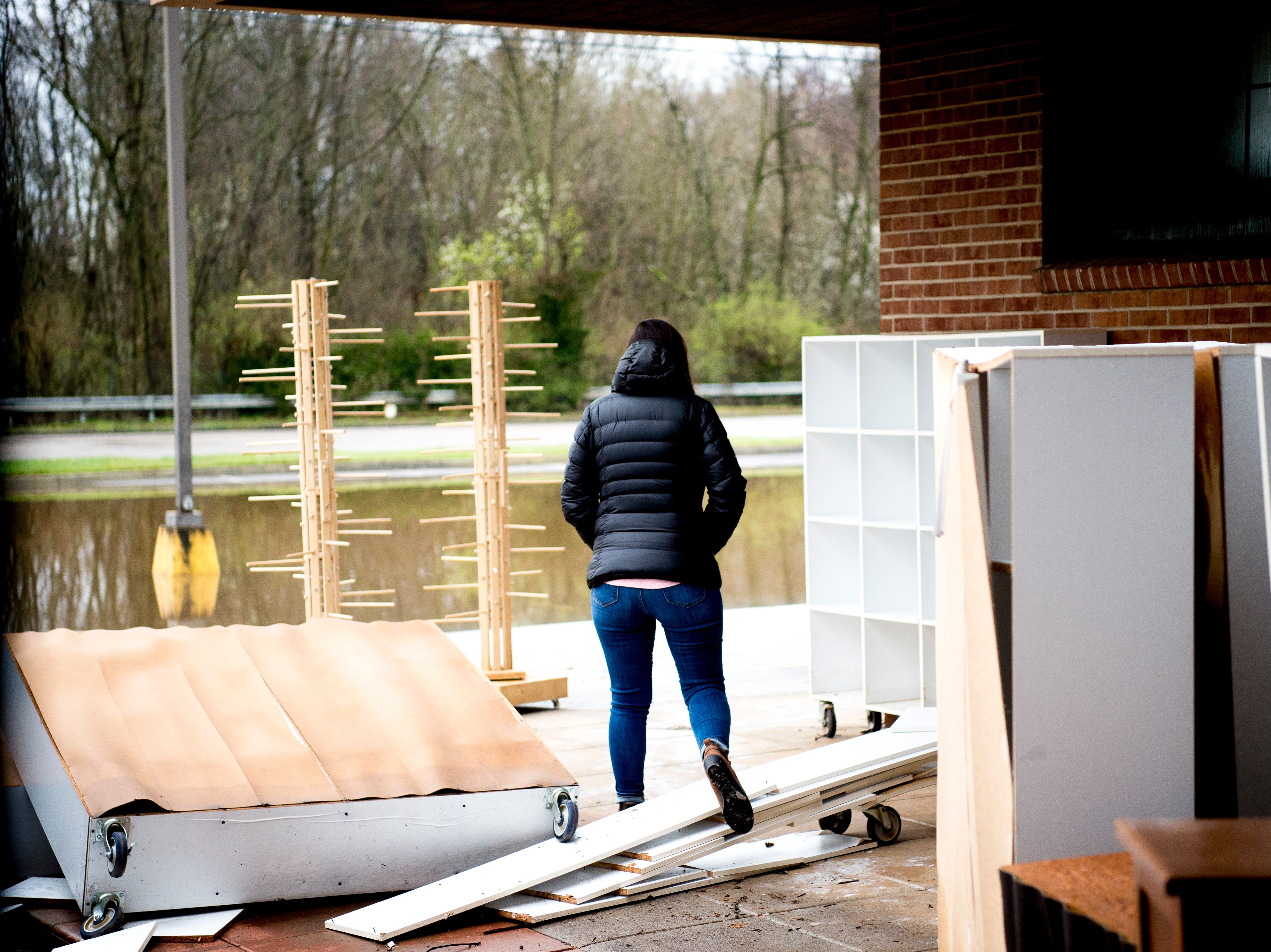A woman steps over debris outside of The Yarn Haven at 464 Cedar Bluff Road in Knoxville, Tennessee on Friday, March 1, 2019. Nearly a quarter of the stores inventory including furniture and paperwork was lost in the floodwaters, which reached over a foot in depth. The owners estimate it will take them a minimum of two months until they can open up shop again.