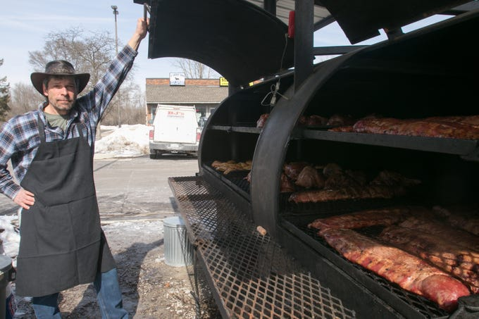 Hotel Hickman Chuckwagon BBQ pit master Pat Purdy holds open the lid of 'Big Bertha,' an outdoor grill cooking ribs, chicken and pork on re-opening day Friday, March 1, 2019 in Hamburg Township.