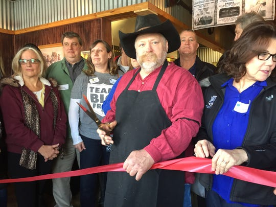 Scott Hickman, center, with scissors, and others prepare to cut a ribbon to mark the seasonal re-opening of Hotel Hickman Chuckwagon BBQ in Hamburg Township Friday, March 1, 2019.