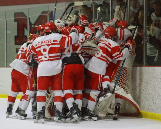 Orchard Lake St. Mary's hockey players celebrate a 2-1 victory over Brighton in a regional semifinal on Thursday, Feb. 28, 2019.
