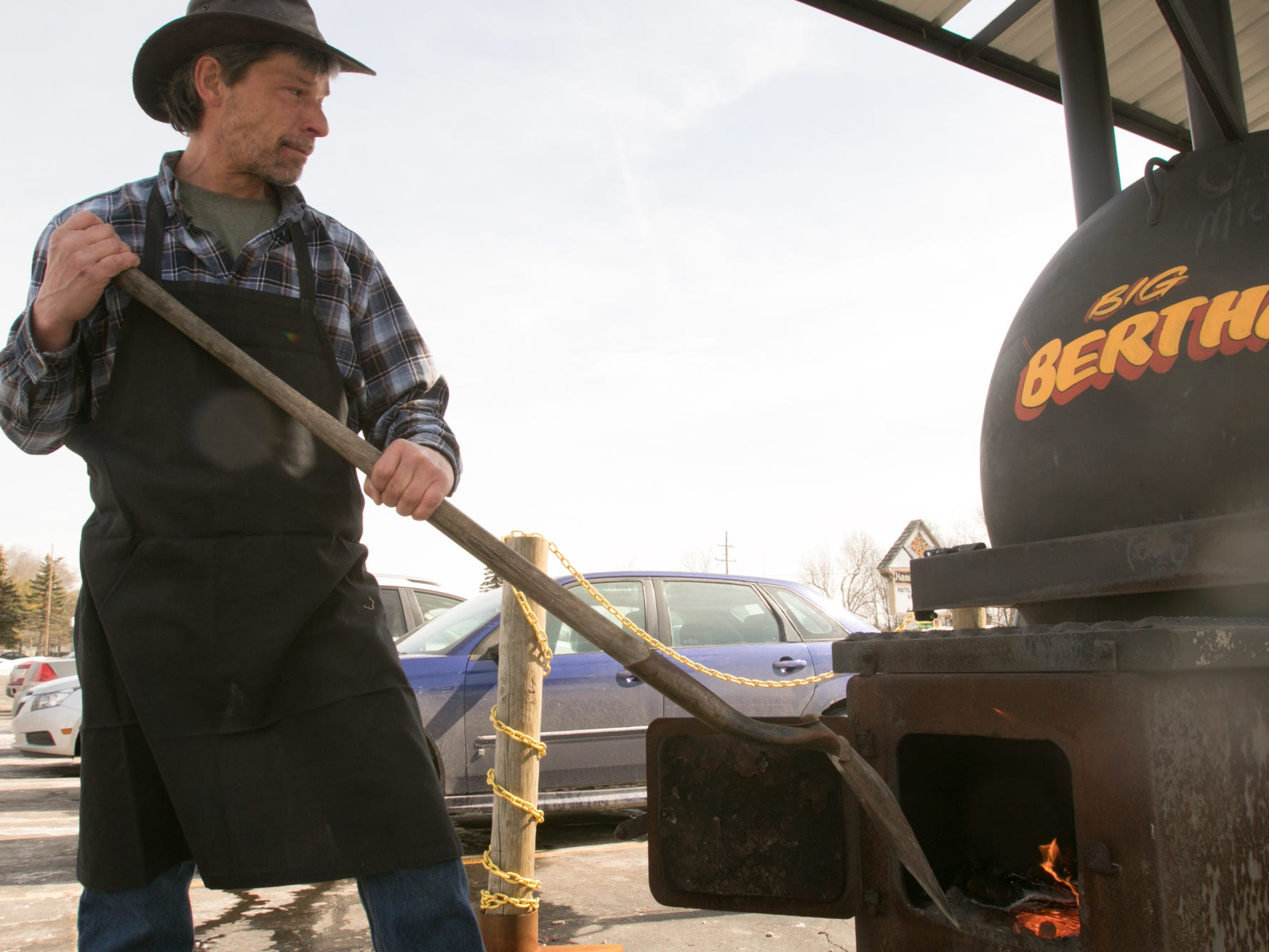 Pat Purdy, pit master at Hotel Hickman Chuckwagon BBQ, stokes the fire built with oak and wild cherry logs in the outdoor grill named 'Big Bertha' Friday, March 1, 2019.