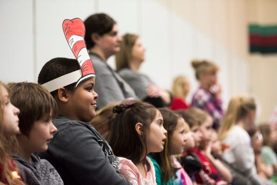 "Dressed as Dr. Seuss' ""Cat in the Hat,"" Gateway North Elementary second grade student Joseph Harps listens to Shane and Chris Houghton, co-creators of the Disney animated TV series ""Big City Greens"" Friday, March 1, 2019, as they talk about their careers."