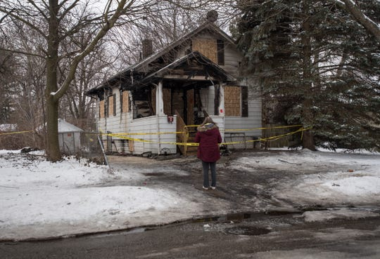 A woman looks at the remnants of a house in the 2300 block of Vine St. on Lansing's east side, which officials say is being investigated for possible arson.