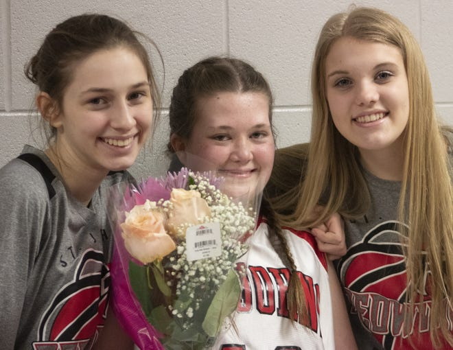 St. Johns junior varsity basketball player Emma Cerny (left), Maddie Peterson (middle) and Carleigh Williams pose for  picture on Tuesday, Feb. 26, 2019. Cerny and Williams helped Peterson, the team manager, get an opportunity to play in Tuesday's game against Charlotte.