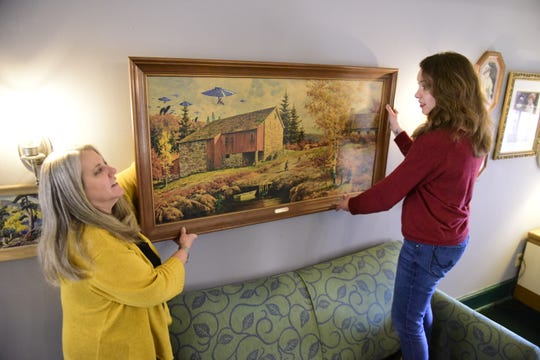 Kathy Fetzer-Goodwin, left, and Llalan Fowler hang an entry to the Monster Painting exhibit at Main Street Books.