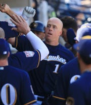 Teammates lineup in the Brewers dugout to congratulate Erik Kratz after his two-run blast against the Giants.