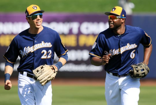 Brewers outfielders Christian Yelich (22) and Lorenzo Cain chat as they head back to the dugout after the top of the second inning against the Giants.