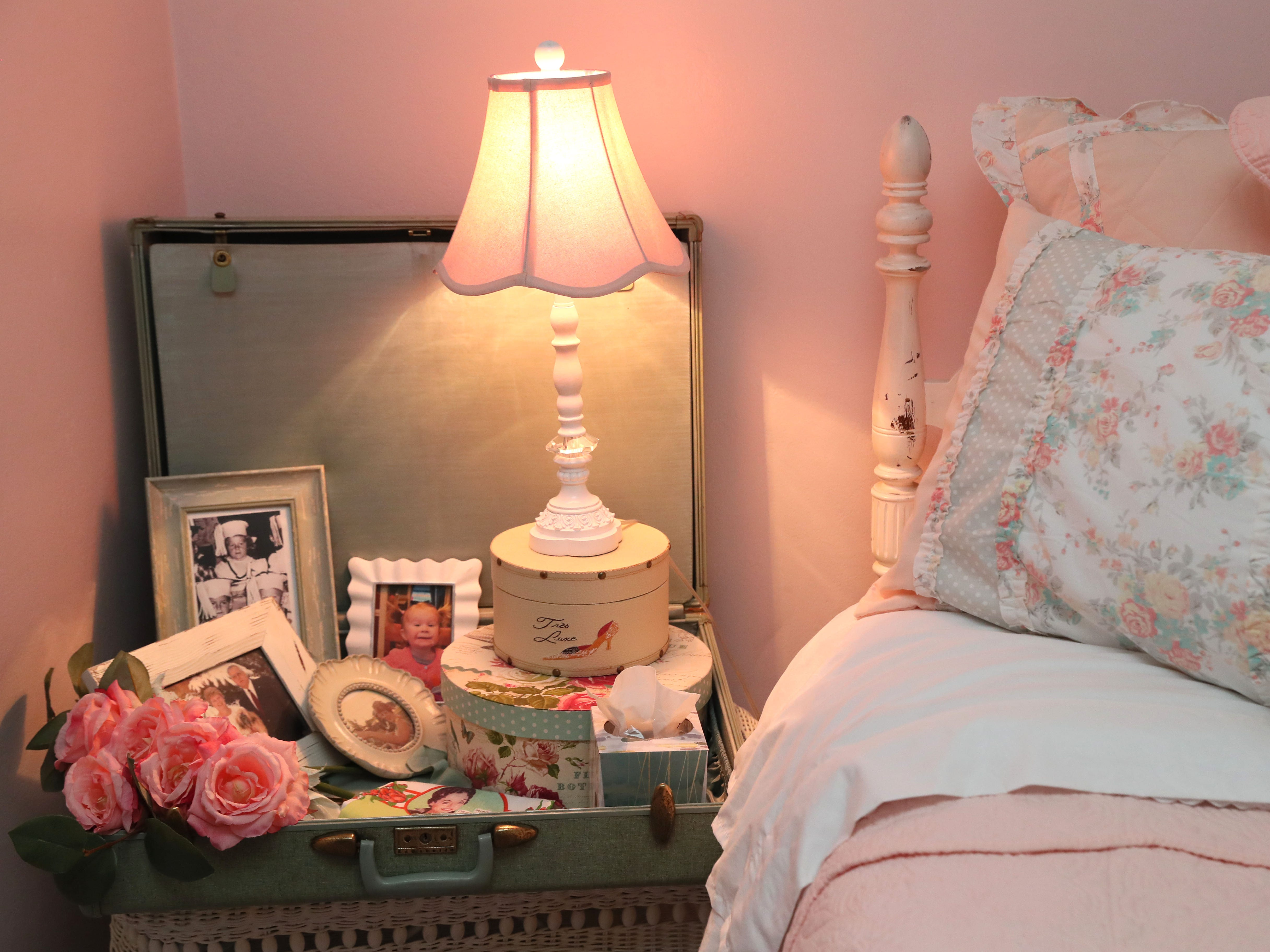 A suitcase in this guest room holds pictures and other decorative objects.
