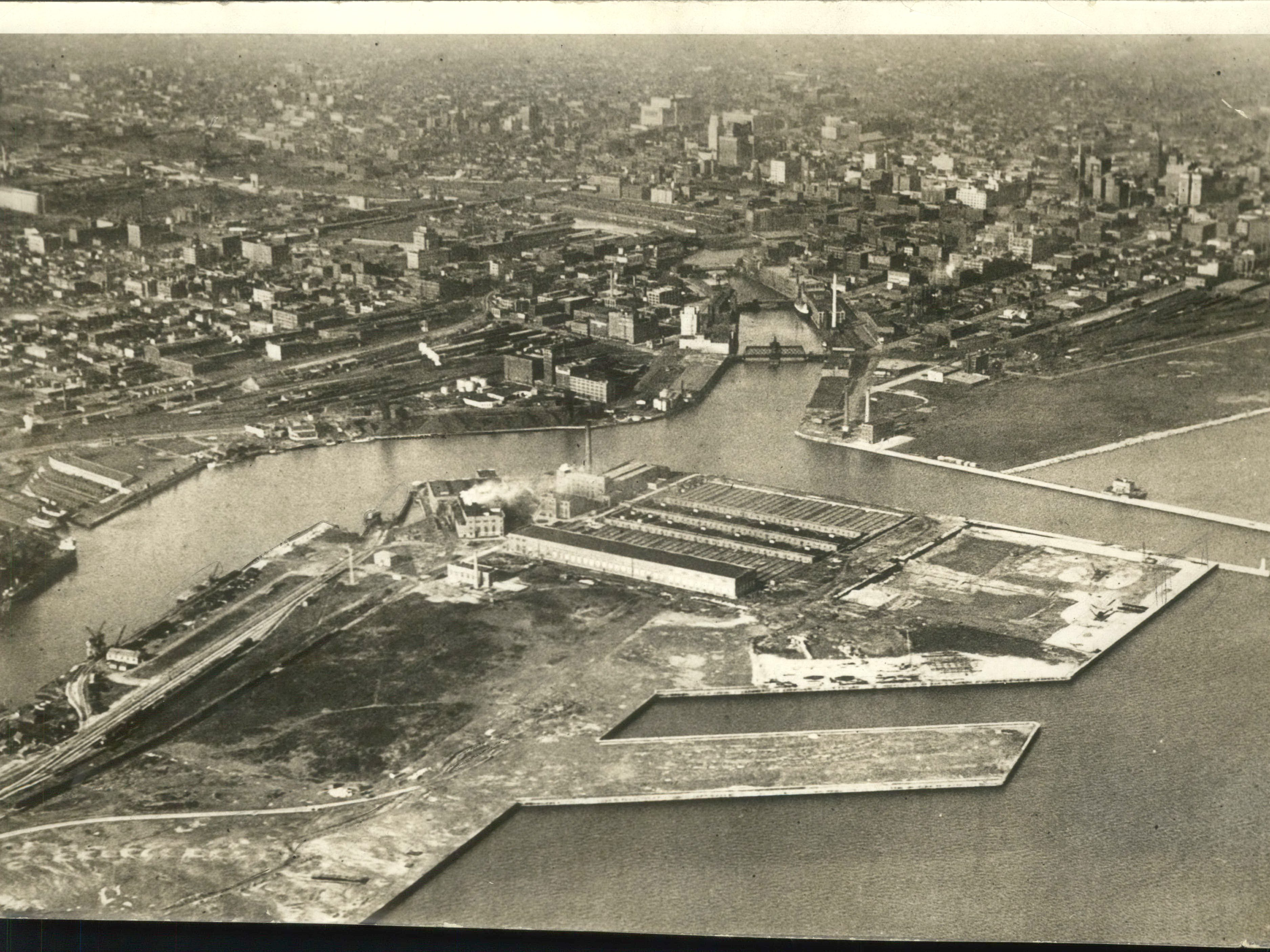 Milwaukee's inner harbor entrance and the municipal development on Jones Island are shown in this picture. In the center at the north end of the sewage disposal plant with land provided for its future extension eastward. In the foreground at the center is pier number 1of the municipal harbor. To the left, along the inner side of the island are the open municipal dock terminal and carferry slips. Picture taken from Mid-west Airways plane. (Air Views)
