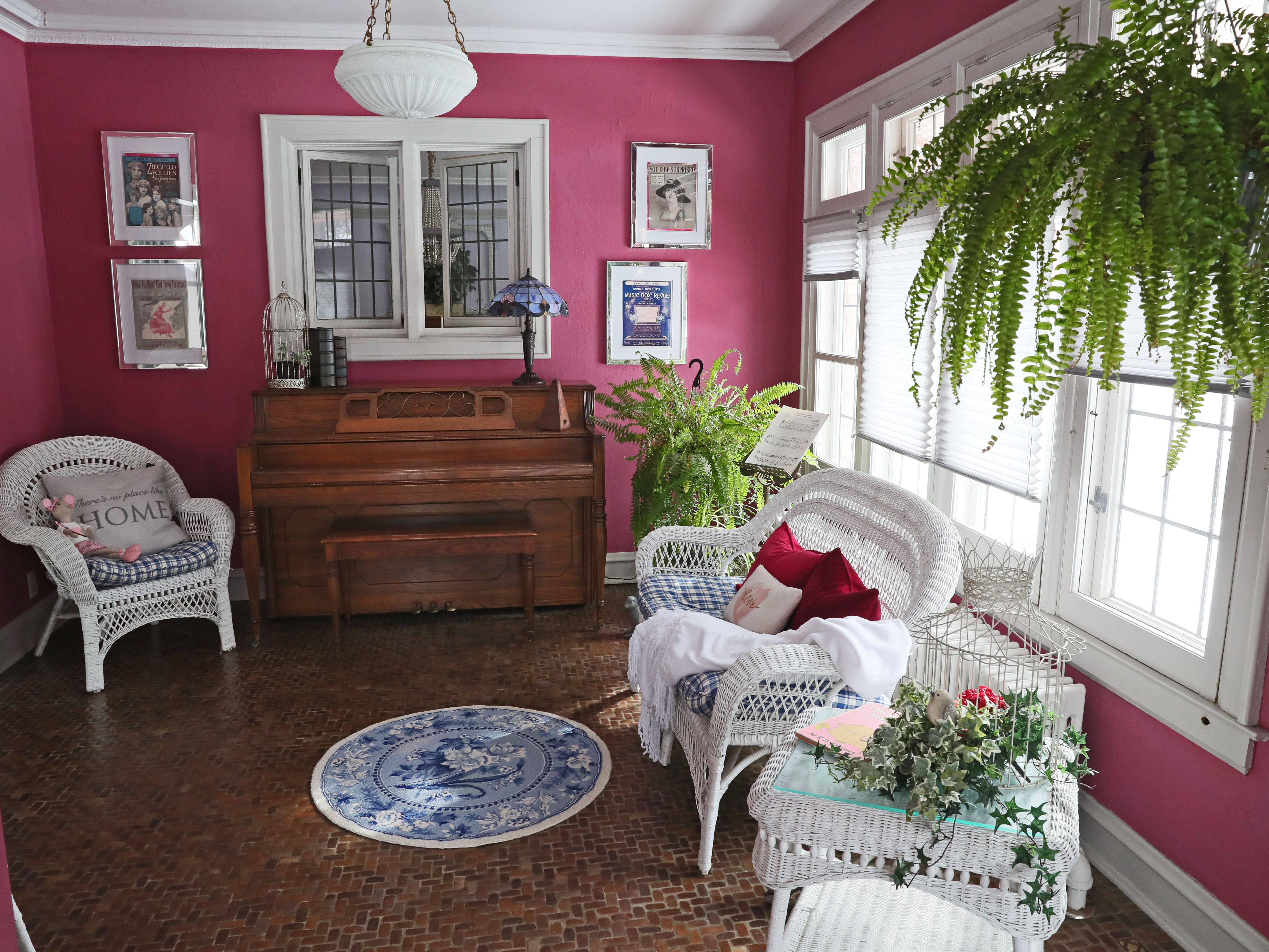The sunroom is painted in the same rose color that she had used in a previous house.