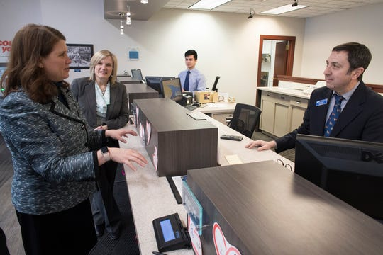 Kathy Blumenfeld (left), secretary-designee of the Wisconsin Department of Financial Institutions, speaks with branch manager Frank Olson during a visit Friday to Prime Financial Credit Union in Milwaukee. In the background is Christine A. Moczynski, president and CEO of Prime Financial..