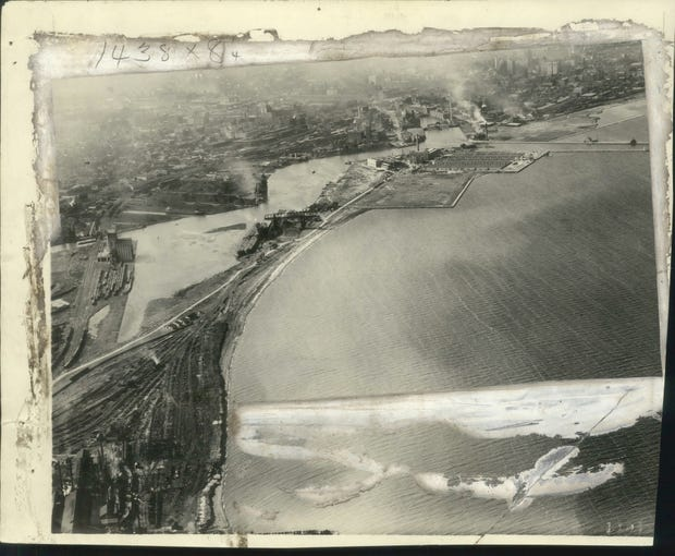 1924: A comprehensive airplane view of Milwaukee's harbor entrance with new sewage disposal plant on top of Jones Island, shown to right of the center. In the background are towering office buildings of downtown.