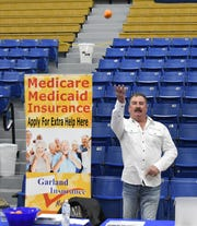 Troy Garland of Garland Insurance tosses an orange into the crowd Friday at the Mountain Home High School Career Expo.