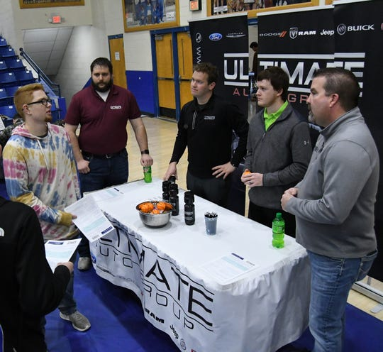 A Mountain Home High School senior talks with employees of Ultimate Auto Group on Friday morning in The Hangar.