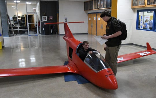 Mountain Home seniors Steven Curtis (seated) and Christian Lamb check out a Bede BD-5 Micro plane on display in the lobby of The Hangar on Friday. The plane was part of a display presented by Chapter 775 of the Experimental Aircraft Association at the Mountain Home High School Career Expo.