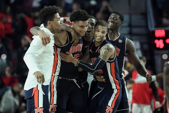 Auburn teammates celebrate with Chuma Okeke (5) after he made the game-winning shot against Georgia on Feb. 27, 2019, in Athens, Ga.