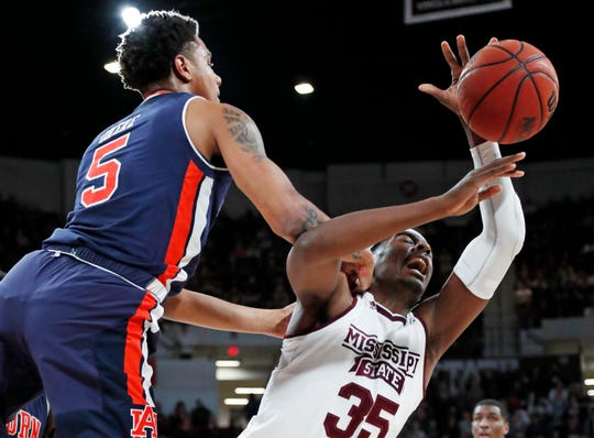 Auburn forward Chuma Okeke (5) falls into Mississippi State forward Aric Holman (35) during the first half of an NCAA college basketball game in Starkville, Miss., Saturday, Jan. 26, 2019.