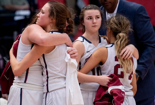 Montgomery Academy's Leighton Robertson hugs  Margaret Head, foreground, and Gabby Ramirez hugs Madi Caddell, background, after losing to Pisgah in the AHSAA 3A championship game at Legacy Arena in Birmingham, Ala., on Friday March 1, 2019.