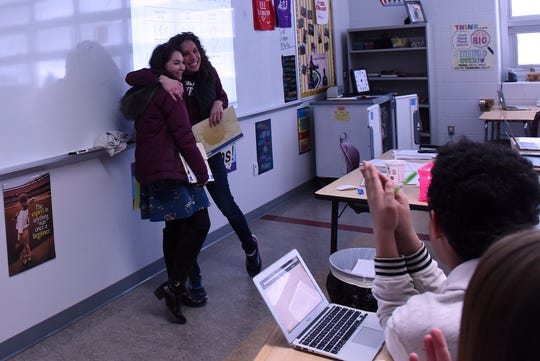 Licking County Foundation Communications and Program Associate Megan Lewis presents Newark High School algebra and financial algebra teacher Amy Hicks with one of the Tibbie Leslie Travel Grants as students applaud. Hicks plans to travel to Italy, Greece and Croatia to learn more about the differences between European and United States economies.