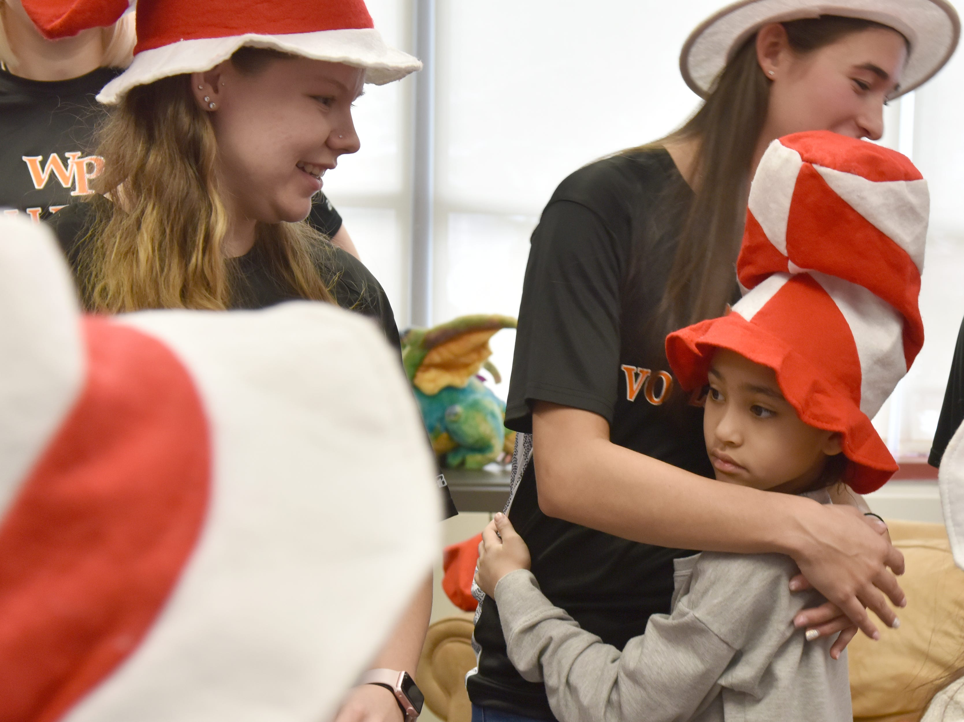 Mia Gonzalez hugs Amanda Lembo, a volleyball player and student teacher at the school. Volleyball players from William Paterson University read to the second grade class at High Mountain Road School in Franklin Lakes on Friday March 1, 2019.