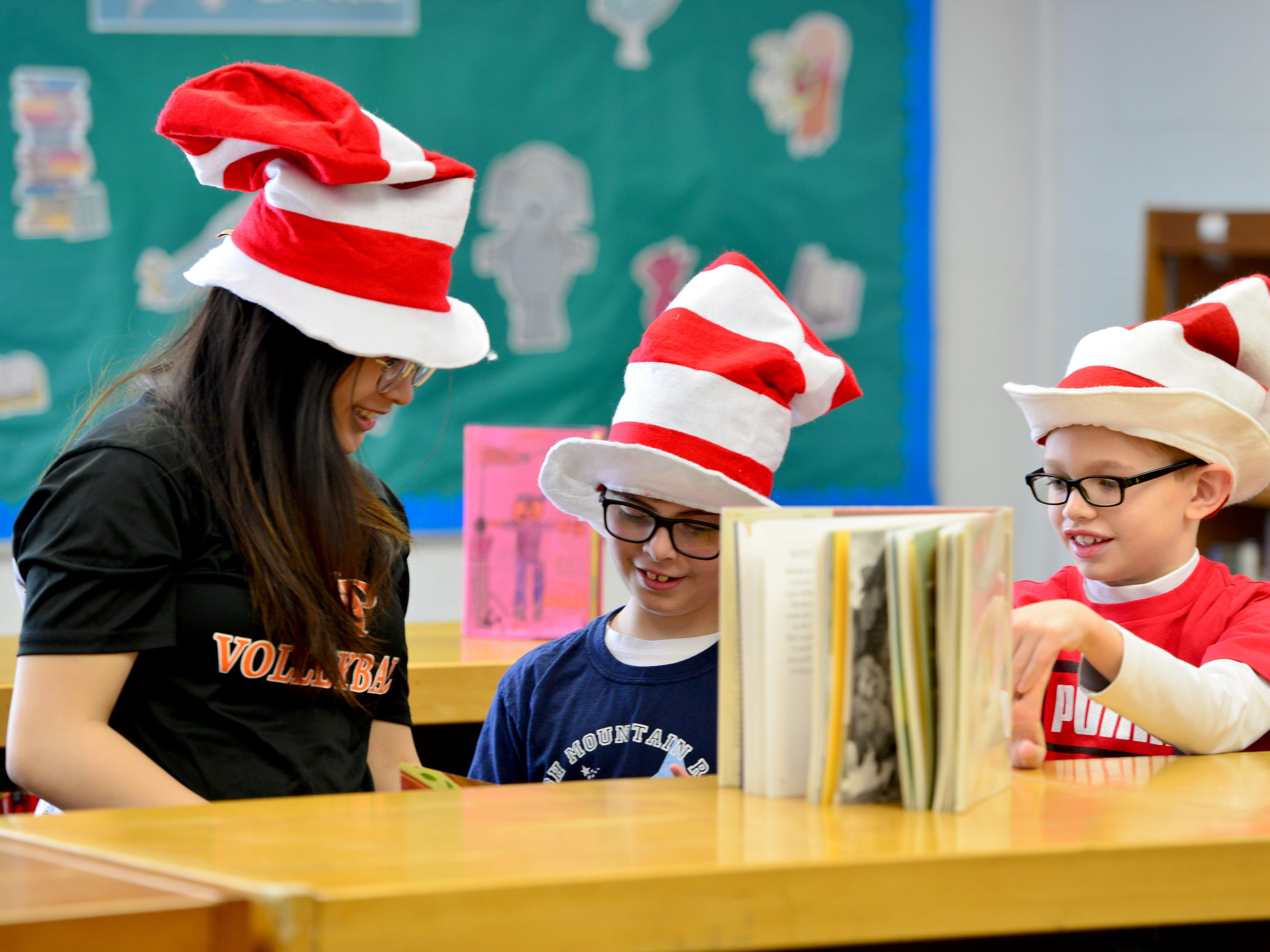 From left, Kyla Sebello looks through the stacks for a book with Harrison Ajaeb and Max Seigel. Volleyball players from William Paterson University read to the second grade class at High Mountain Road School in Franklin Lakes on Friday March 1, 2019.