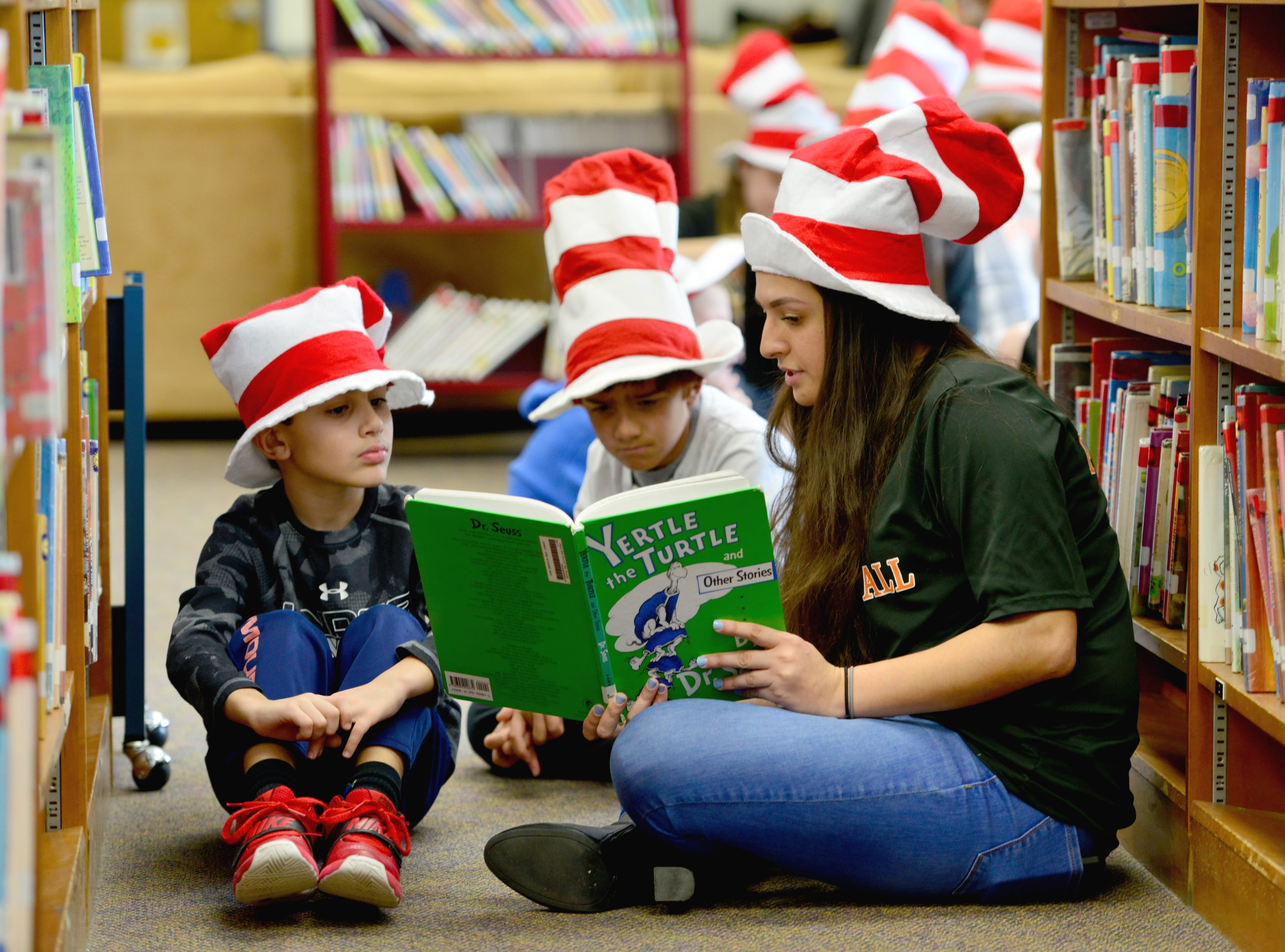 From right, Julianna Ginefra read to Dilan Sharma and Gregory Alashaian. Volleyball players from William Paterson University read to the second grade class at High Mountain Road School in Franklin Lakes on Friday March 1, 2019.