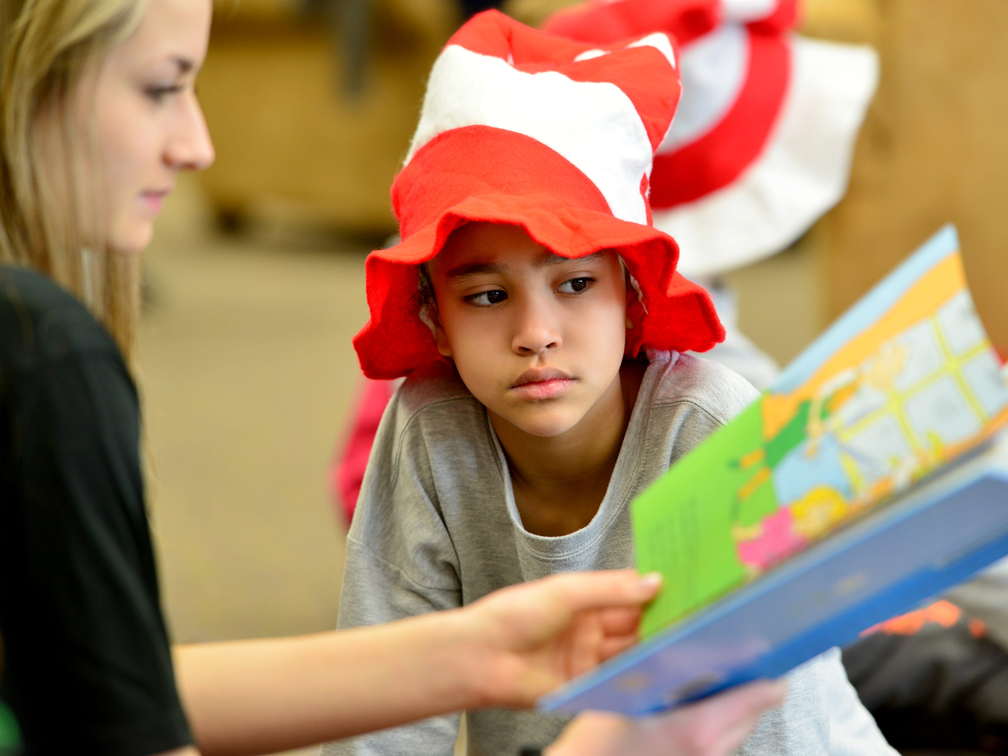 Mia Gonzalez listens to Kristin Volavka read to her. Volleyball players from William Paterson University read to the second grade class at High Mountain Road School in Franklin Lakes on Friday March 1, 2019.