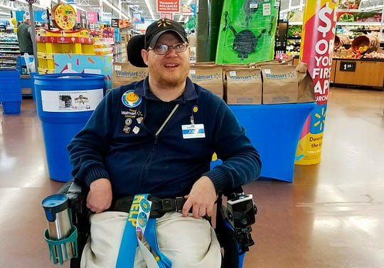 """In this April 21, 2018 photo provided by Rachel Wasser, Walmart greeter John Combs works at a Walmart store in Vancouver, Wash. Combs, who has cerebral palsy, and other greeters with disabilities are threatened with job loss as Walmart transforms the greeter position into one that's more physically demanding.  After more than a week of backlash, Greg Foran, president and CEO of Walmart's U.S. stores, said in a memo to store managers Thursday, Feb. 28, 2019, that """"we are taking some specific steps to support"""" greeters with disabilities.  (Rachel Wasser via AP)"""