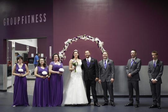 Bride Andi Nevue and groom Daniel Butler pose for a photo with their wedding party at Crunch Fitness, where they were married on Feb. 14, 2019.