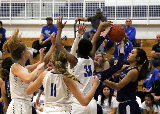 Carlsbad's Dayshaun Moore (30) gets a block on a Clovis player during Thursday's Class 4-5A semifinal game.