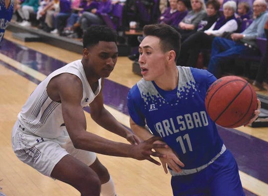 Carlsbad junior Matt Fernandez works along the baseline tightly guarded by Clovis senior Darion Morgan during the Wildcats' 60-36 win Thursday at Rock Staubus Gymnasium.