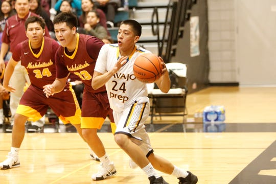 Navajo Prep's Treston Yazzie dribbles along the baseline toward the basket against Tohatchi's Elijah Tsosie (33) and Ashtyn Burbank (34) during Thursday's District 1-3A tournament semifinals game at the Eagles Nest.