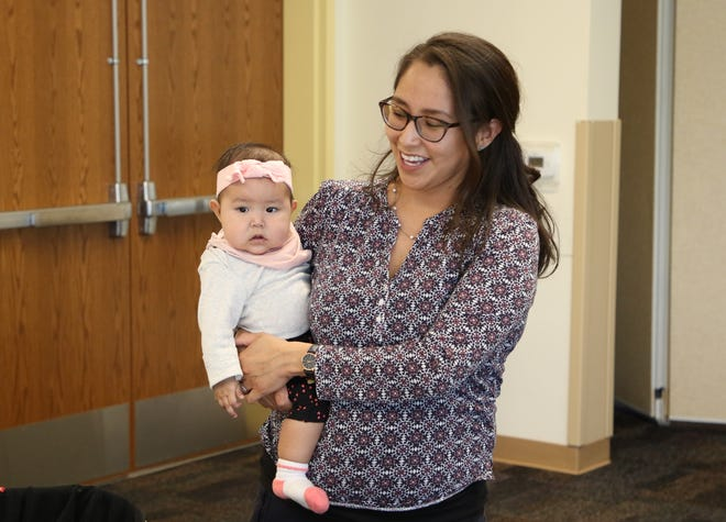 Dara Livingston and her daughter, Lucy Livingston, visit with coworkers during a gathering Friday in Farmington for the Navajo Women, Infants and Children Program. Dara is a nutritionist for Navajo WIC's Gallup Program and has been nursing Lucy at work.