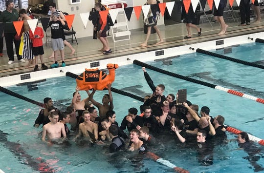 The Northville boys swim and dive team celebrates winning the KLAA championship.