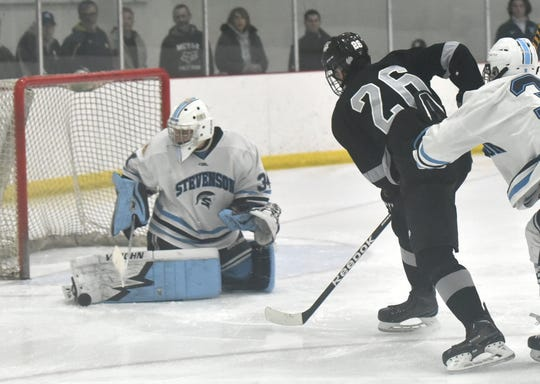 Stevenson goalie Eric Polzin stops a near point-blank shot by Wildcat Jack VanDenBeaugeury on Feb. 28. The puck is seen by Polzin's right leg pad.