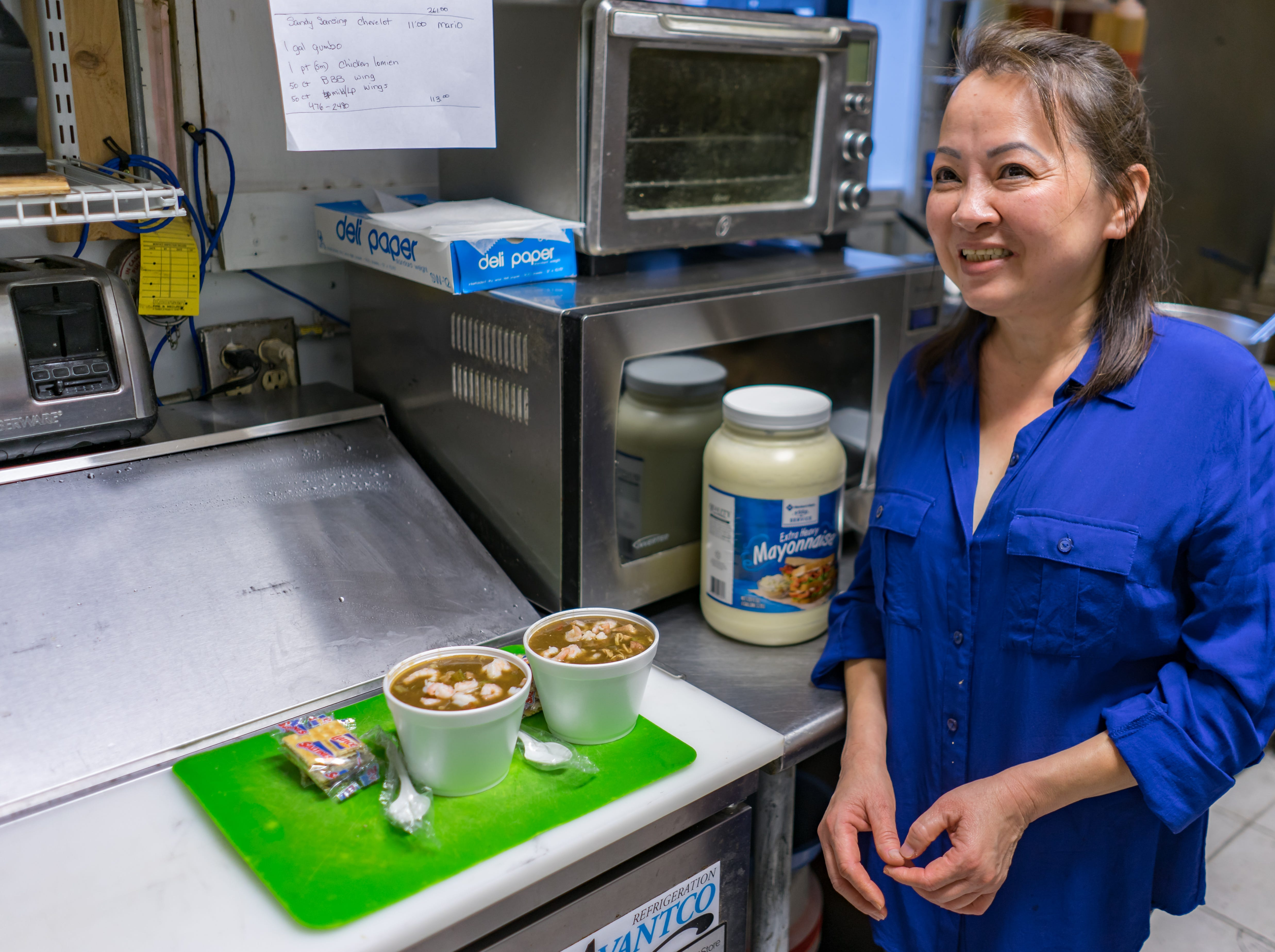 """Tran Huonggiang, the mastermind behind a 100-gallon-per-week gumbo operation at Green Acre Convenient Store, finishes preparing two """"small"""" cups of gumbo on Friday, March 1, 2019."""