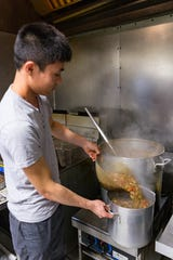 Owen Truong, Tran Huonggiang's son-in-law, transfers gumbo into a smaller pot before storing the larger quantity for later use on Friday, March 1, 2019.