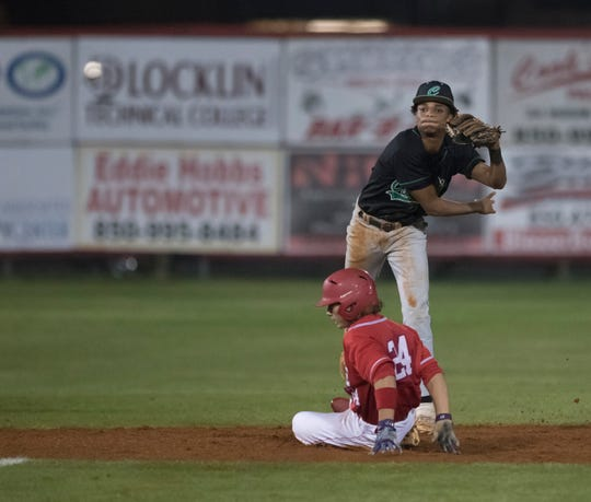 Caleb Vincent (24) slides into second base as Jordan McCants (23) turns a double play during the Catholic vs Pace baseball game at Pace High School on Thursday, February 28, 2019. Jordan McCants committed to Mississippi State on July 13, 2019.
