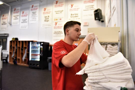 Alex Lecrone folds towels at the north Hanover YMCA on Feb. 21, 2019.