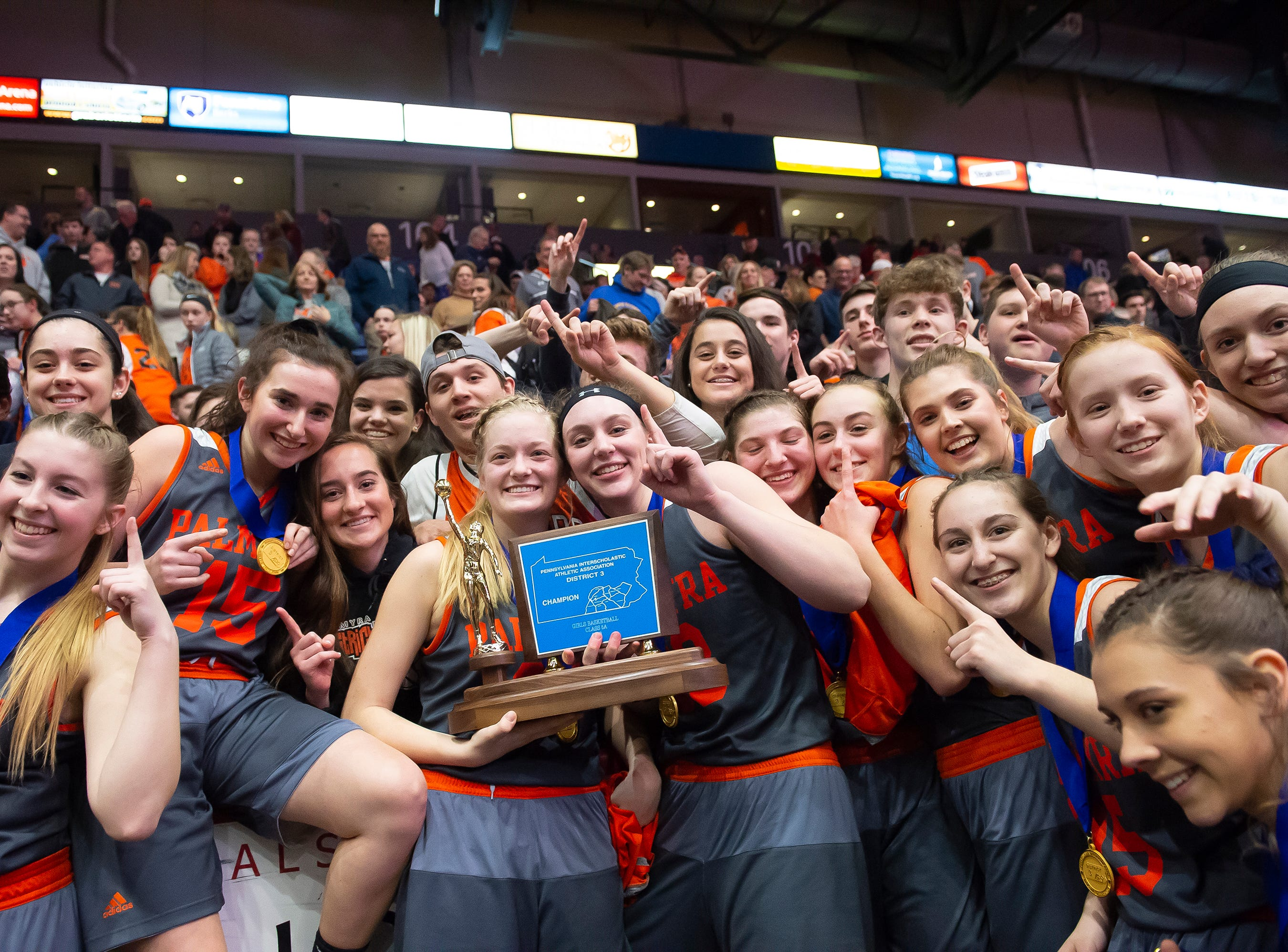 Palmyra players pose with the student section after defeating Gettysburg in the District 3 5A girls championship game at Santander Arena in Reading, Pa., Friday, March 1, 2019. The Cougars won 31-23.