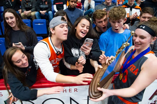 Palmyra's Olivia Richardson shows off the District 3 5A girls championship trophy with the student section after the Cougars downed Gettysburg at Santander Arena in Reading, Pa., Friday, March 1, 2019.