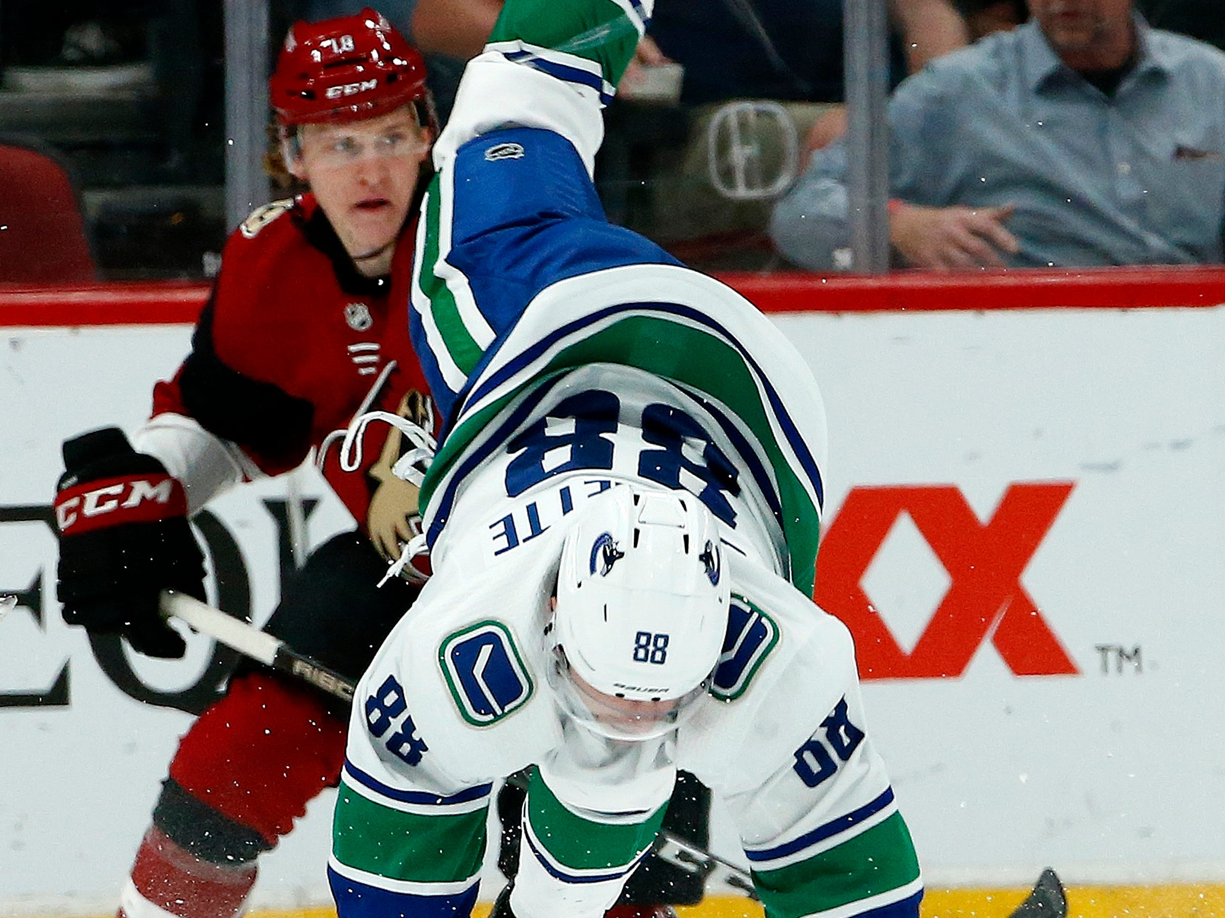 Vancouver Canucks center Adam Gaudette (88) gets upended on a kneeing penalty by Arizona Coyotes' Conor Garland as Coyotes center Christian Dvorak, left, watches the movement of the puck during the first period of an NHL hockey game Thursday, Feb. 28, 2019, in Glendale, Ariz.