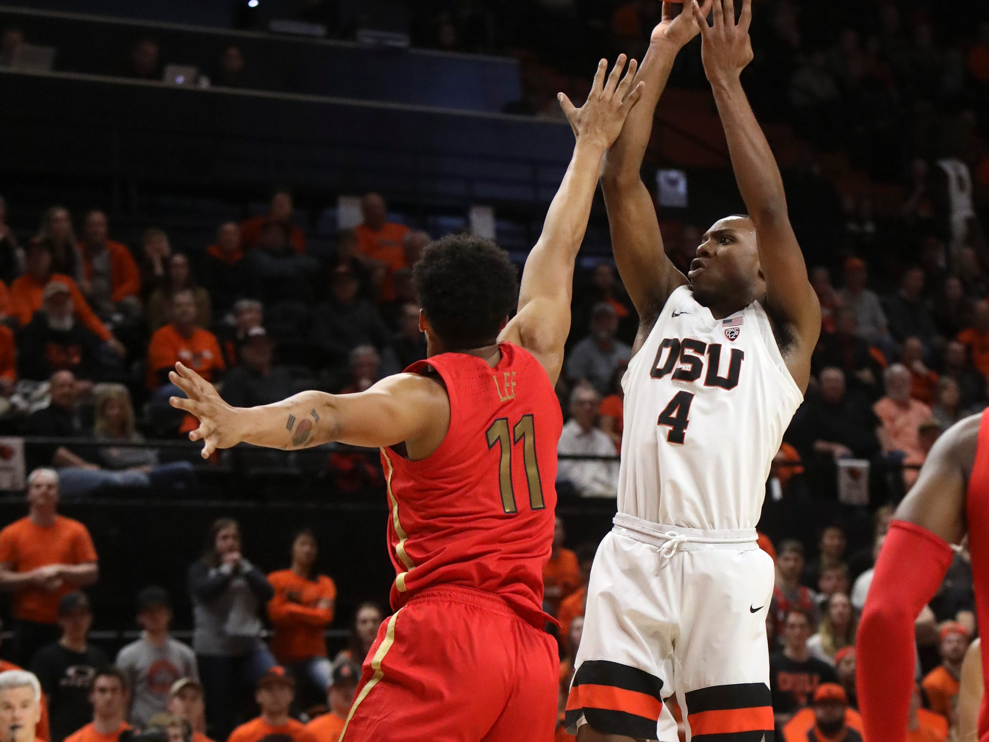 Oregon State's Alfred Hollins (4) takes a shot despite defense from Arizona's Ira Lee (11) during the first half of an NCAA college basketball game in Corvallis, Ore., Thursday, Feb. 28, 2019.