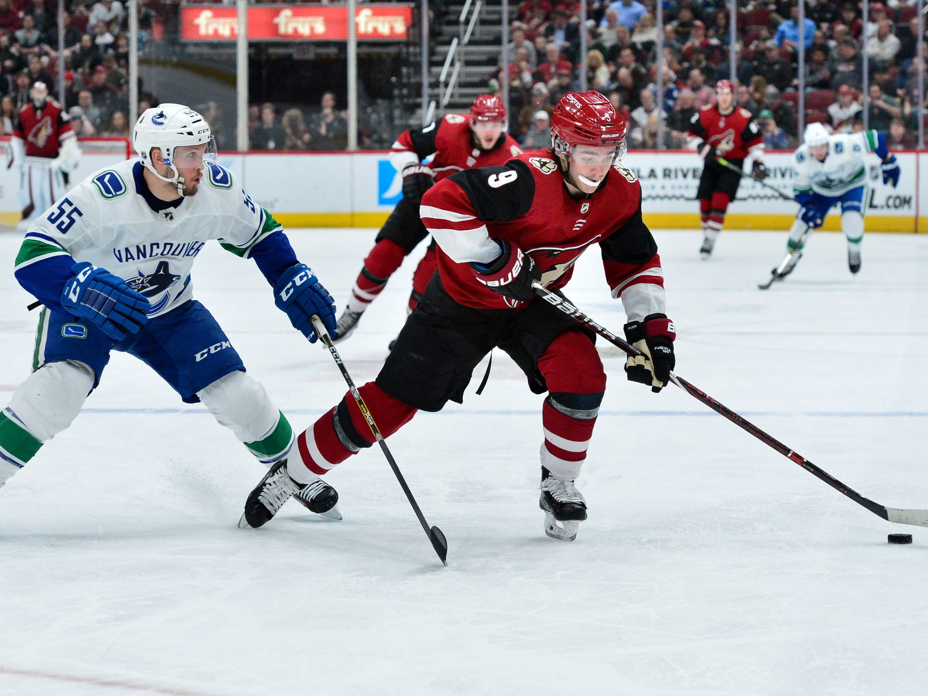Feb 28, 2019; Glendale, AZ, USA; Arizona Coyotes center Clayton Keller (9) skates with the puck as Vancouver Canucks defenseman Alex Biega (55) defends during the second period at Gila River Arena.